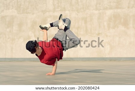 Young boy dancing break dance on the street - stock photo
