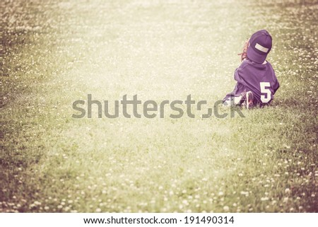 Young boy daydreaming in the outfield - stock photo