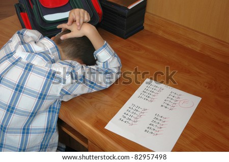 Young boy depressed because of math test - stock photo
