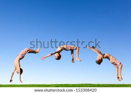 Young boy doing a backflip on a green meadow - stock photo