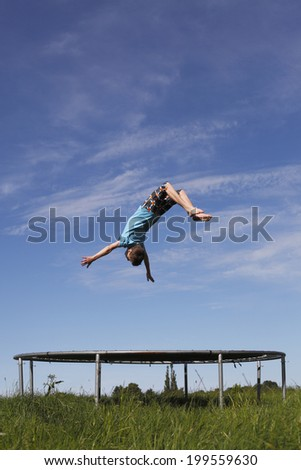 Young boy doing a backflip on a trampoline on green meadow