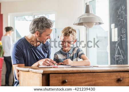 Young boy doing his school homework with his father, the boy is writing in his book, at the blurred background the mother works in the kitchen - stock photo