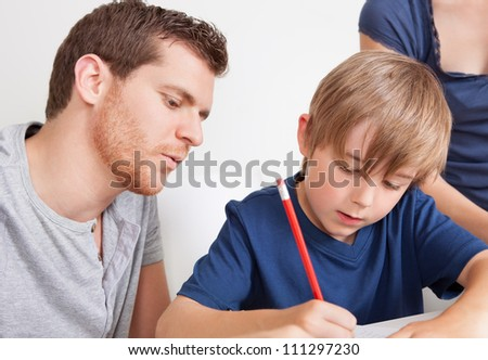 Young boy doing homework together with his father - stock photo