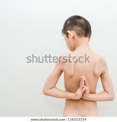 young boy doing yoga exercise in Virasana or Hero Pose with reversed prayer or namaste in studio against a mottled background from behind. - stock photo