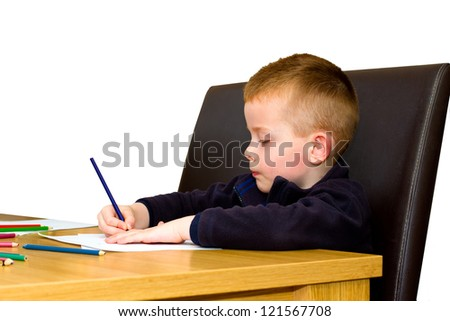 young boy drawing with pencils on a table