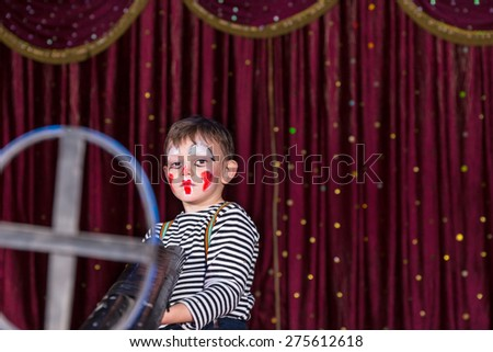Young Boy Dressed as Clown Holding Large Double Barreled Gun with Iron Sight, Standing on Stage with Red Curtain - stock photo