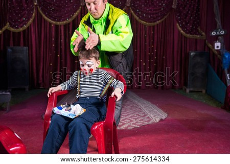 Young Boy Dressed as Clown Sitting in Chair with Tray of Make Up on Lap on Stage, Man Wearing Bright Jacket with Hands Positioned on Top of Boys Head