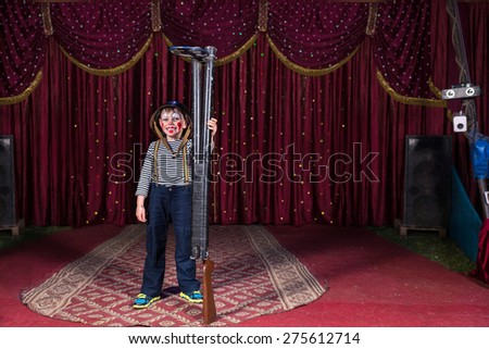 Young Boy Dressed as Clown Wearing Combat Helmet Smiling and Standing on Stage Holding Barrels of Shot Gun with Over Sized Barrels - stock photo