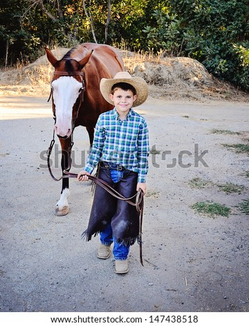 Young boy dressed as Cowboy leading Paint Horse