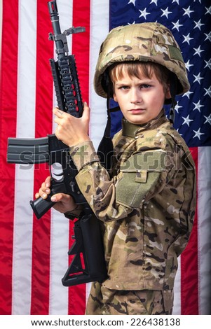 Young boy dressed like a soldier with rifle and American flag in background. - stock photo