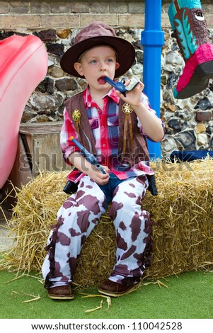 Young boy dressed up as a cowboy - stock photo
