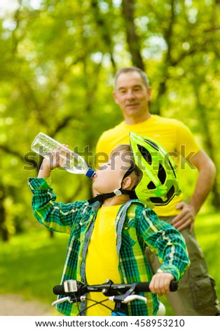 Young boy drink water is learning to ride a bike with his grandfather