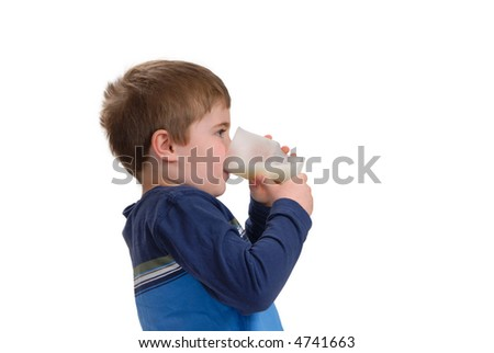 Young boy drinking a glass of milk, isolated on white with copy space - stock photo