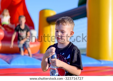 Young boy drinking bottled water as he stands in front of a colorful plastic jumping castle at a playground or fairground
