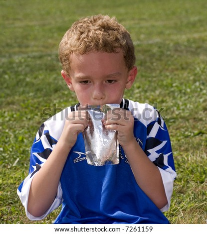Young boy drinking from a pouch at soccer game halftime - stock photo