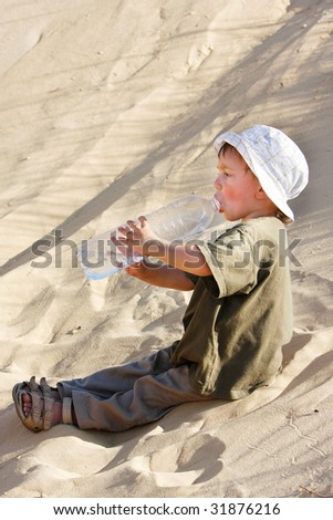 young boy drinking water in sand desert - stock photo