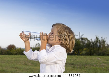 Young boy drinking water whilst playing outdoors on the grass - stock photo