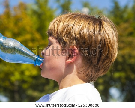 young boy drinks water out of a bottle after sports - stock photo
