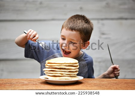 Young boy eating a stack of pancakes.