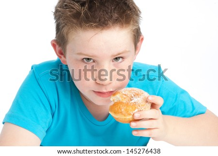 Young boy eating a sugary doughnut. Isolated on a white background. - stock photo