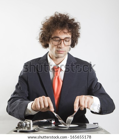 young boy eating a vinyl record on a turntable - stock photo