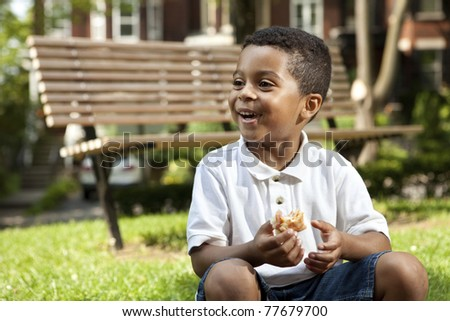 Young boy eating at a park - stock photo