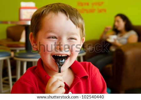 Young boy eating chocolate frozen yogurt at frozen yogurt or ice cream shop - stock photo