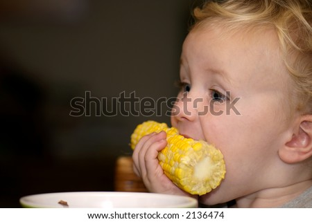 Young boy eating corn for dinner