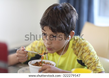 Young boy eating dinner - with shallow depth of field