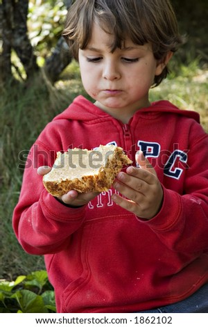 young boy eating peanut butter sandwich - stock photo