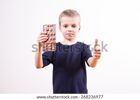 Young boy eats chocolate tablet