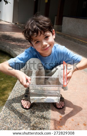 Young boy enjoying a day catching and feeding fish in pond - stock photo