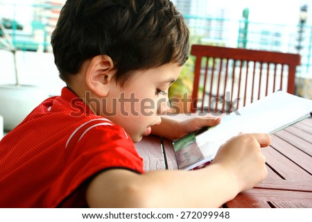 Young boy enjoying his story book. - stock photo