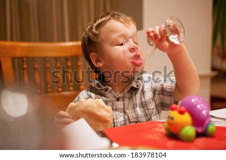 Young boy enjoying lunch draining the last drops of liquid from a glass as he holds a pie in his other hand - stock photo