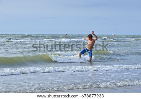 Young boy enjoying to play with water in the waves
