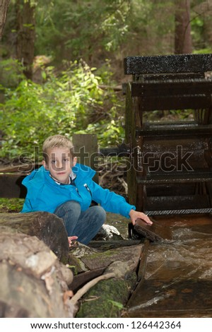 Young boy exploring and squatting down to investigate an old water wheel in lush woodland - stock photo
