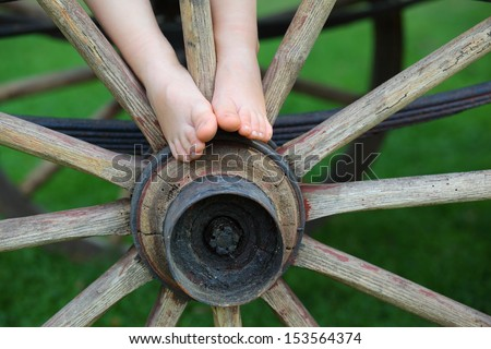 Young boy feet on the axle of a vintage wooden-spoked wheel/Rural Childhood - stock photo