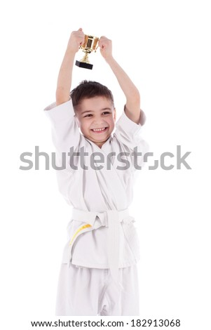 Young boy fighter winner in white kimono with cup - stock photo