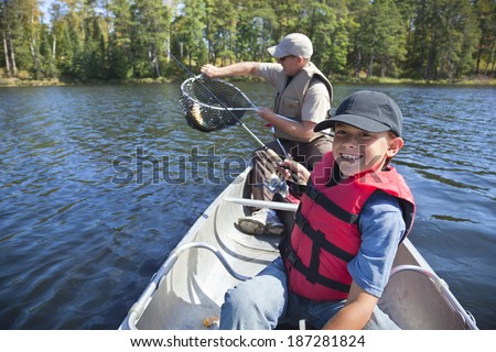 Young boy fisherman smiles while his dad takes the fish out of the net - stock photo
