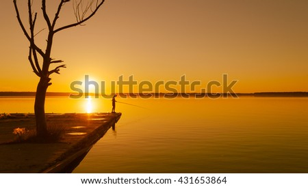 Young boy fishing on a lake at sunset near dead tree - stock photo