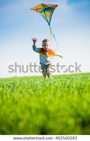 Young boy flies his kite in an open field. Little kid playing with kite on green meadow. Childhood concept.