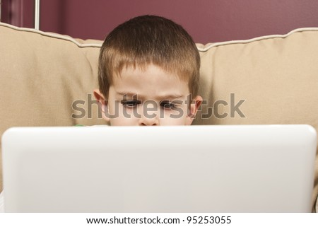 Young boy focuses on a netbook computer