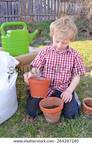 Young boy gardening outdoors. - stock photo