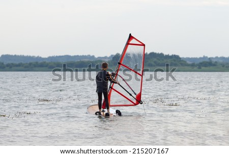 Young boy getting windsurfing lessons along a mild shoreline