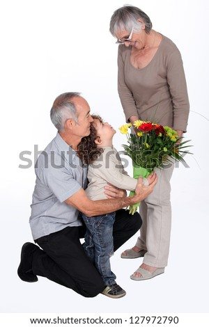 Young boy giving his grandma flowers