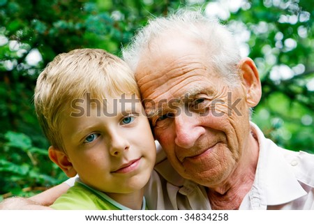 young boy - grandchild, and his grandfather - old man - stock photo