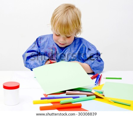 Young boy happily cutting his way into a sheet of paper on a table filled with colorful pencils, glue en felt pens