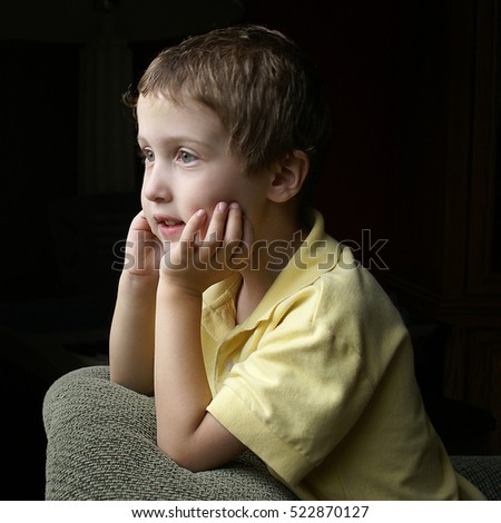 Young boy happily eagerly looking out window, portrait, dark background