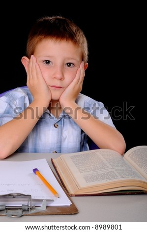 Young boy hard at work studying his books