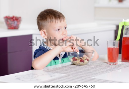 Young Boy Having Breakfast at Kitchen Table, Enjoying Bowl of Oatmeal Cereal with Cherries on Top and Glass of Red Juice